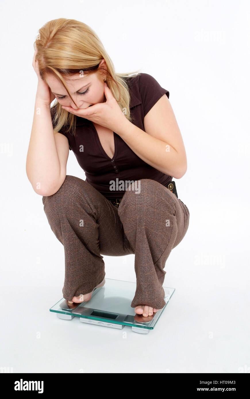 Juneg Frau Erschrickt Beim Blick Auf Die Waage - schockiert Frau im Maßstab Stockbild