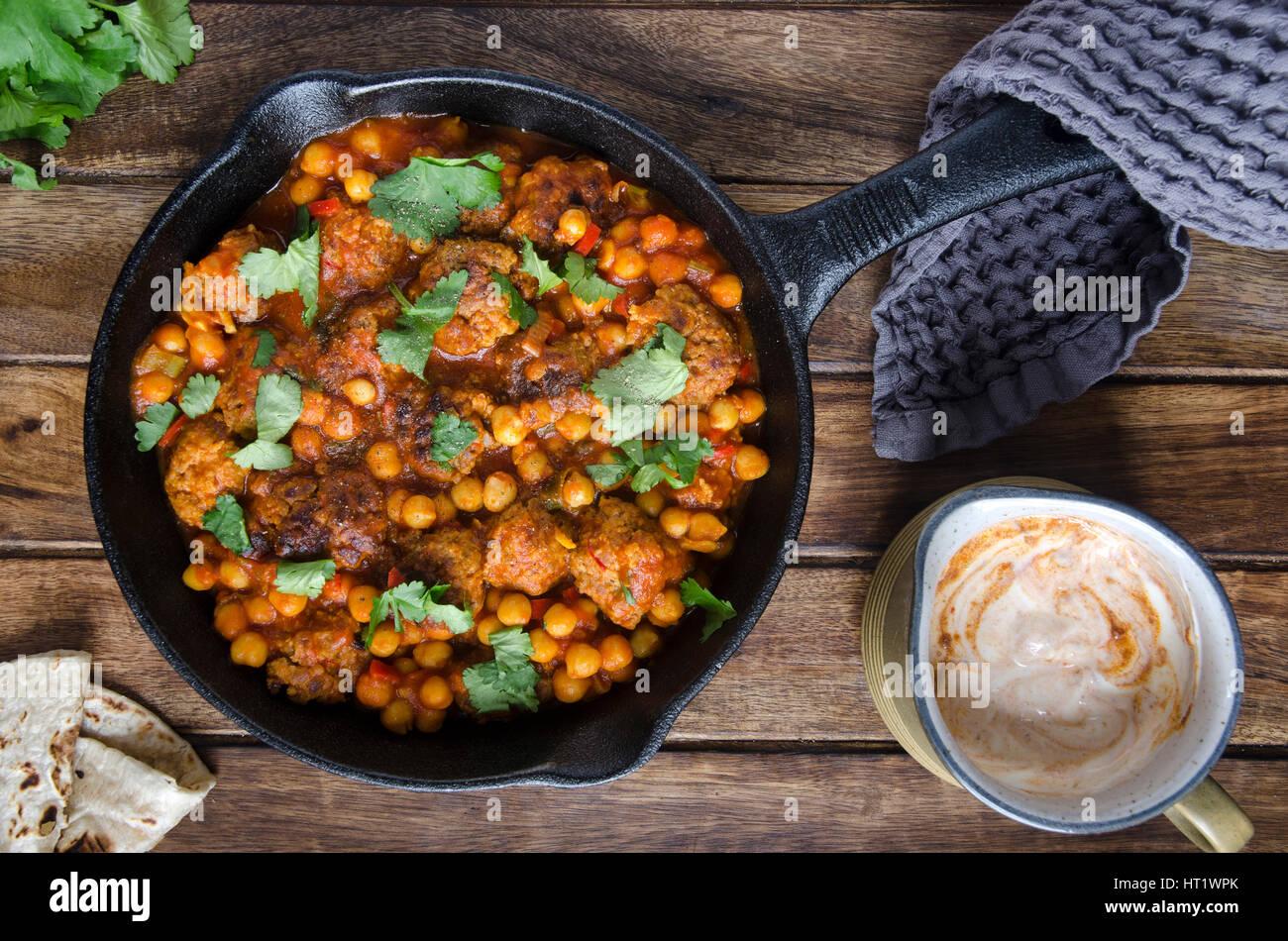 Schweinefleischbällchen mit Kichererbsen und Harissa Joghurt Stockbild