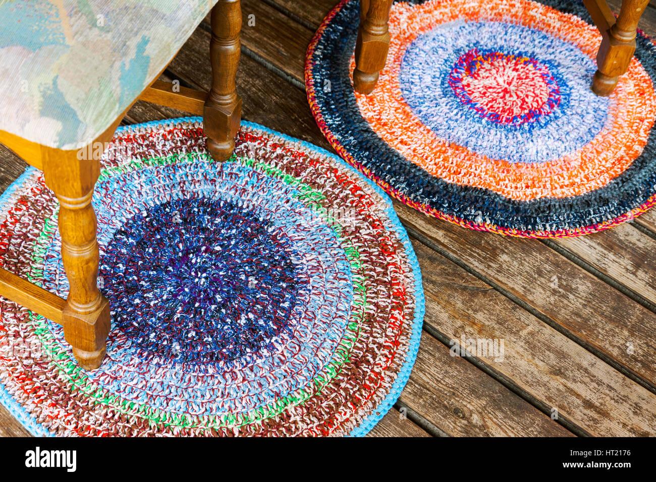 Zwei handgefertigte bunte Teppiche auf einem Holzfußboden mit ein paar Stühle Stockfoto