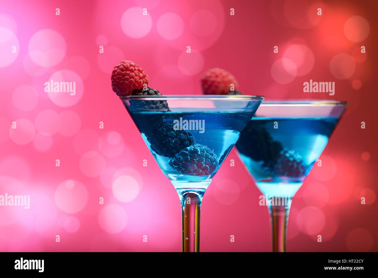 Bunte Cocktails, garniert mit Beeren, Hintergrund mit Lichteffekten Stockfoto