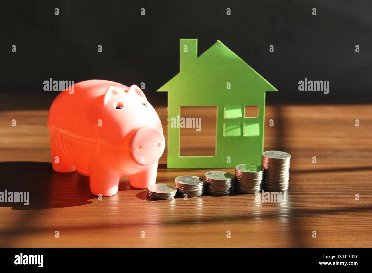 Sparen Geld, Haus oder zu Hause zu kaufen. Sparschwein mit Münzen Stockbild