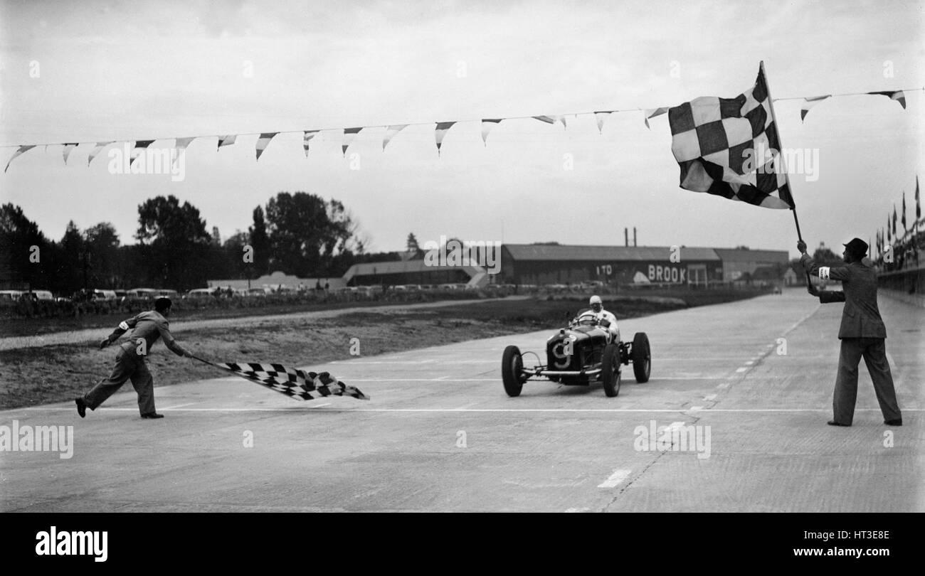 Alfa Romeo unter dem Chequred-Flag in einem Rennen in Brooklands. Künstler: Bill Brunell. Stockbild
