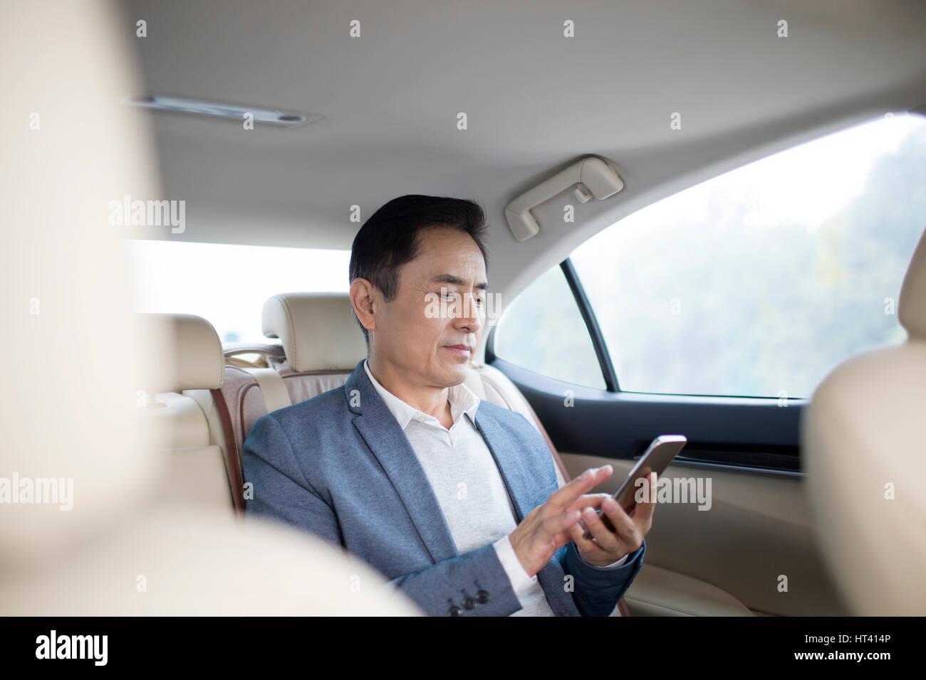 Geschäftsmann mit Smartphone im Auto Stockfoto