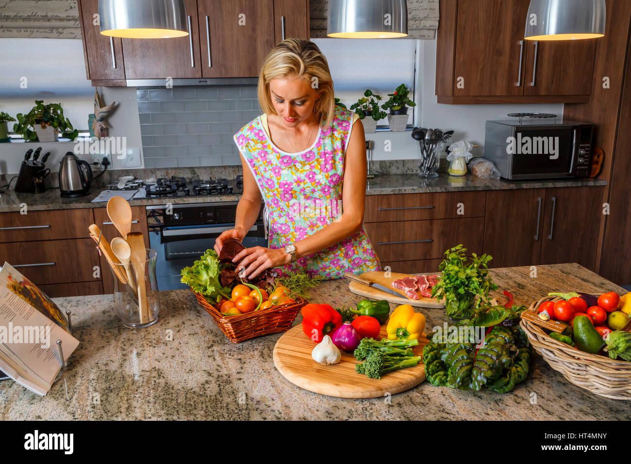 Eine langhaarige blonde junge Frau Zubereitung einer Mahlzeit in der Küche mit frischen gesunden gesundes Produkt. Stockbild