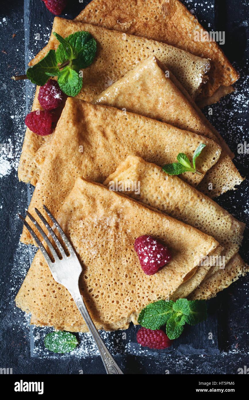 Köstliche hausgemachte Vollkorn Crêpes serviert mit frischen Himbeeren, Minze Blätter und Zucker Stockbild