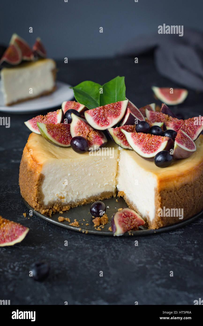 Leckere New York Käsekuchen mit frischen Feigen und schwarzen Trauben. Nahaufnahme. Stockbild