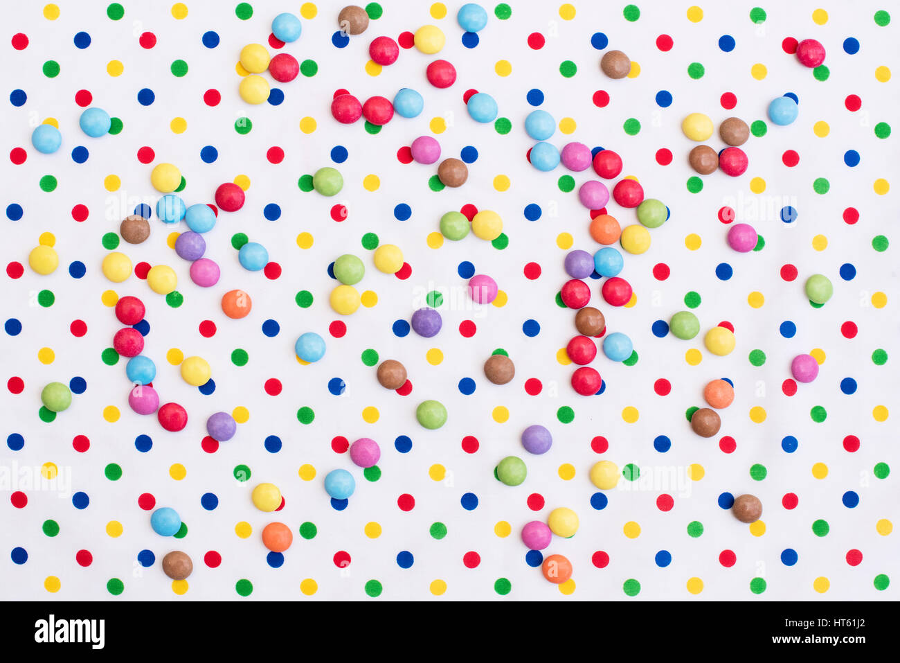Smarties auf bunte Polka Dot Tischdecke. Muster Stockbild