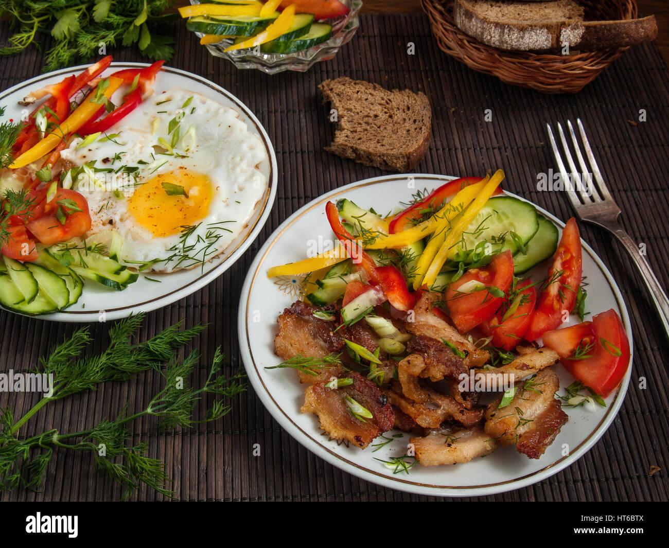 Gebratener Speck, Eiern und Gemüse mit Paprika, Tomaten und grünen auf weißen Platten auf einem Tisch Stockbild