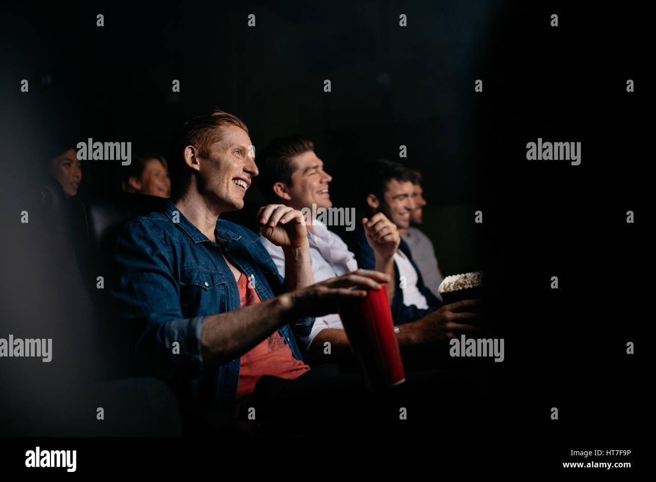 Lächelnd jungen Mann mit Freunden im Kinofilm Halle beobachten. Gruppe von Menschen Film im Theater. Stockbild