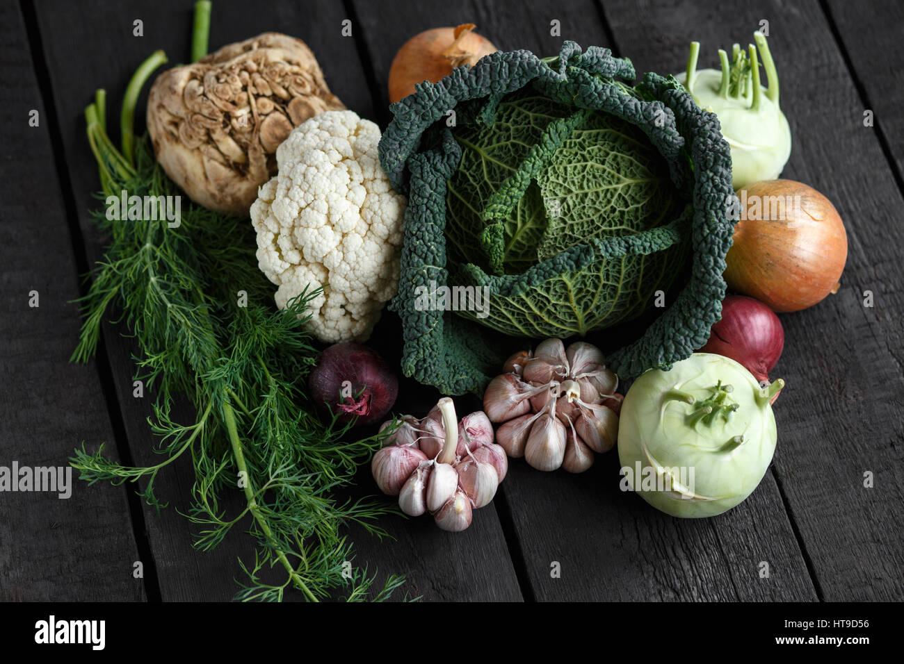 Frühling Gemüse auf einem dunklen Hintergrund: Wirsing, Blumenkohl, Zwiebeln, Knoblauch, Kohlrabi, Sellerie, Stockbild