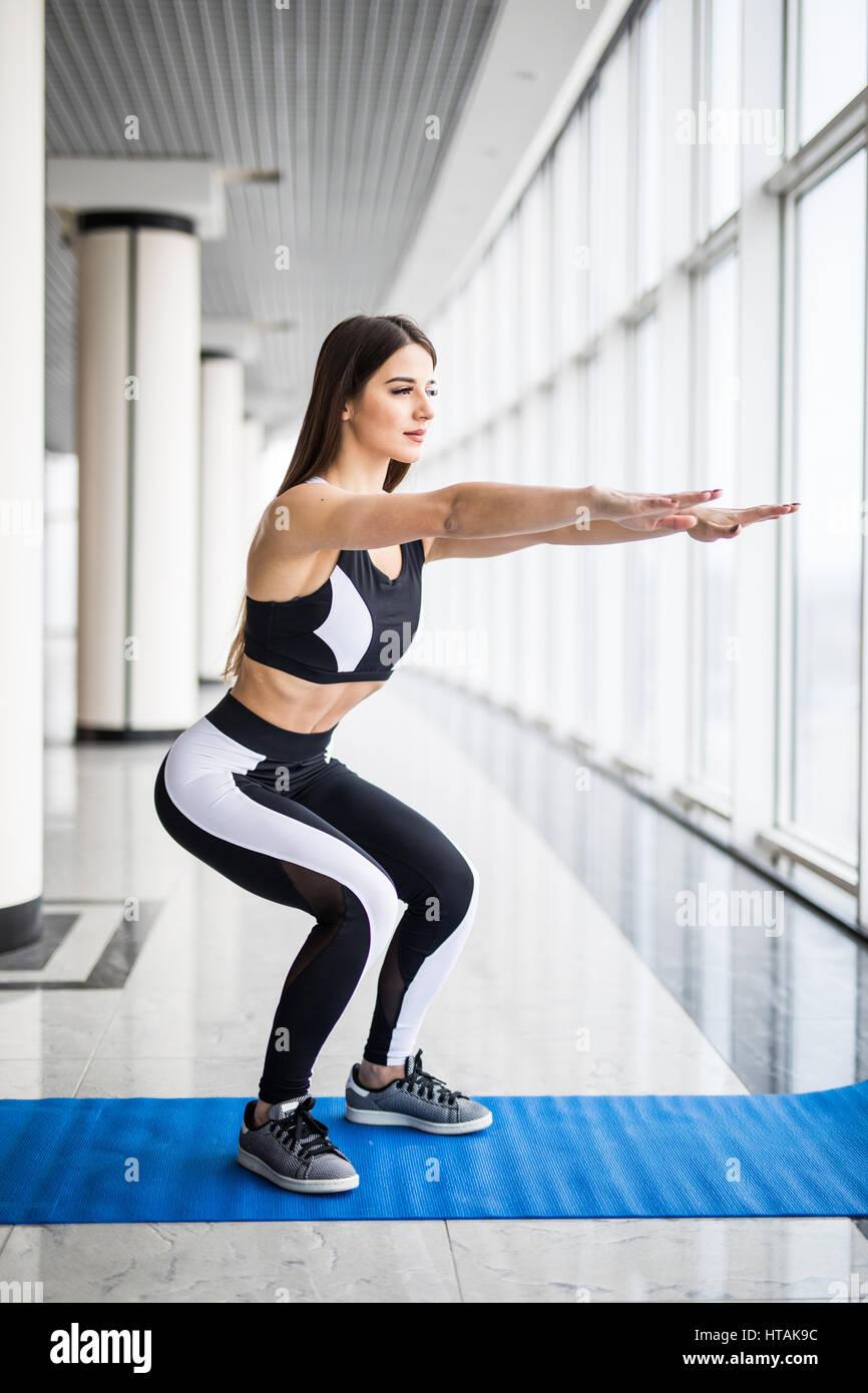 Tiefe Kniebeugen. Seitenansicht der schöne Frau Sportswear hocken zu tun und halten Hanteln stehen im Vordergrund Stockbild