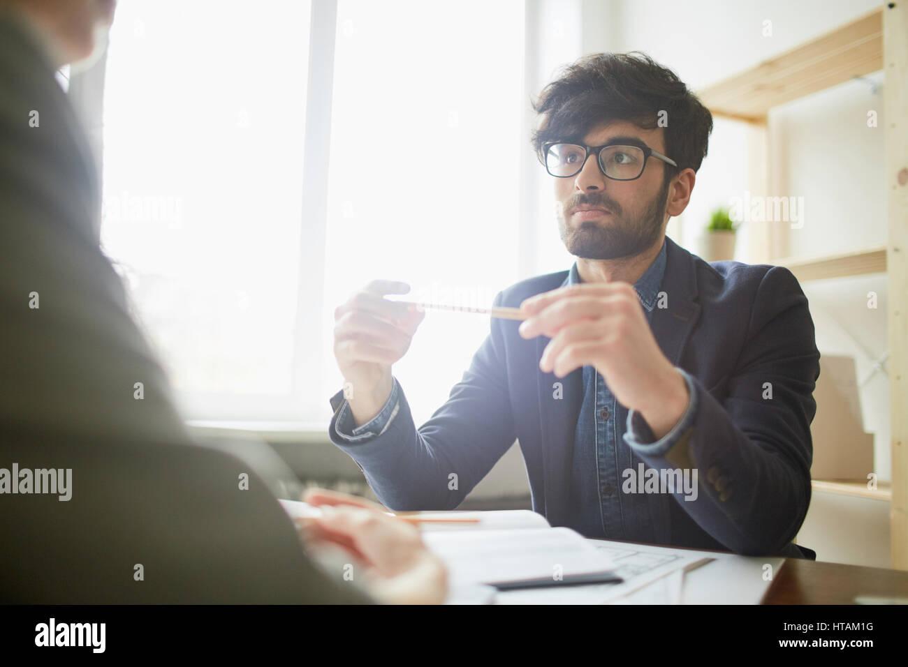 Porträt des jungen kreativen nahöstlichen Geschäftsmann Brille lauschte seinem Partner sitzt ihm Stockbild