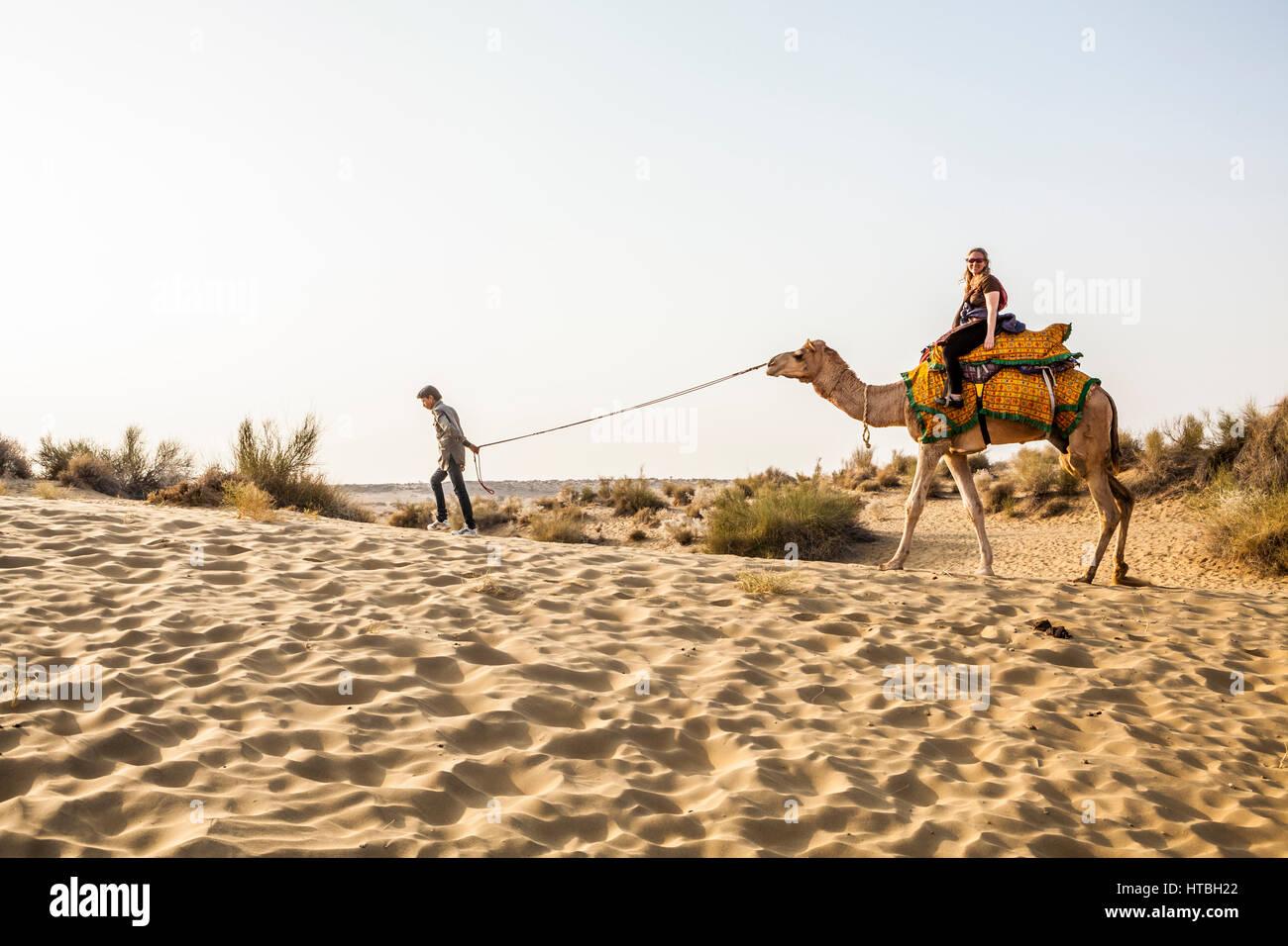 Eine Frau, ein Kamel, angeführt von ihrem Kamel Fahrer in der Thar-Wüste von Westindien in der Nähe Stockbild
