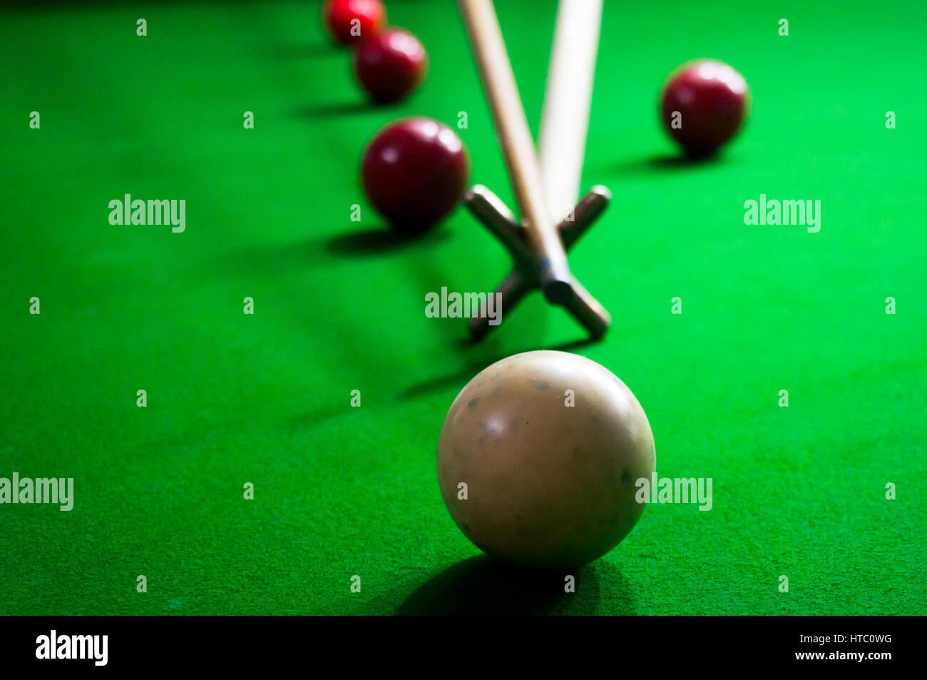 mit Hilfe eines Spider-Sticks in eine Partie Snooker Pool oder Billard zu weit hergeholt Stockbild