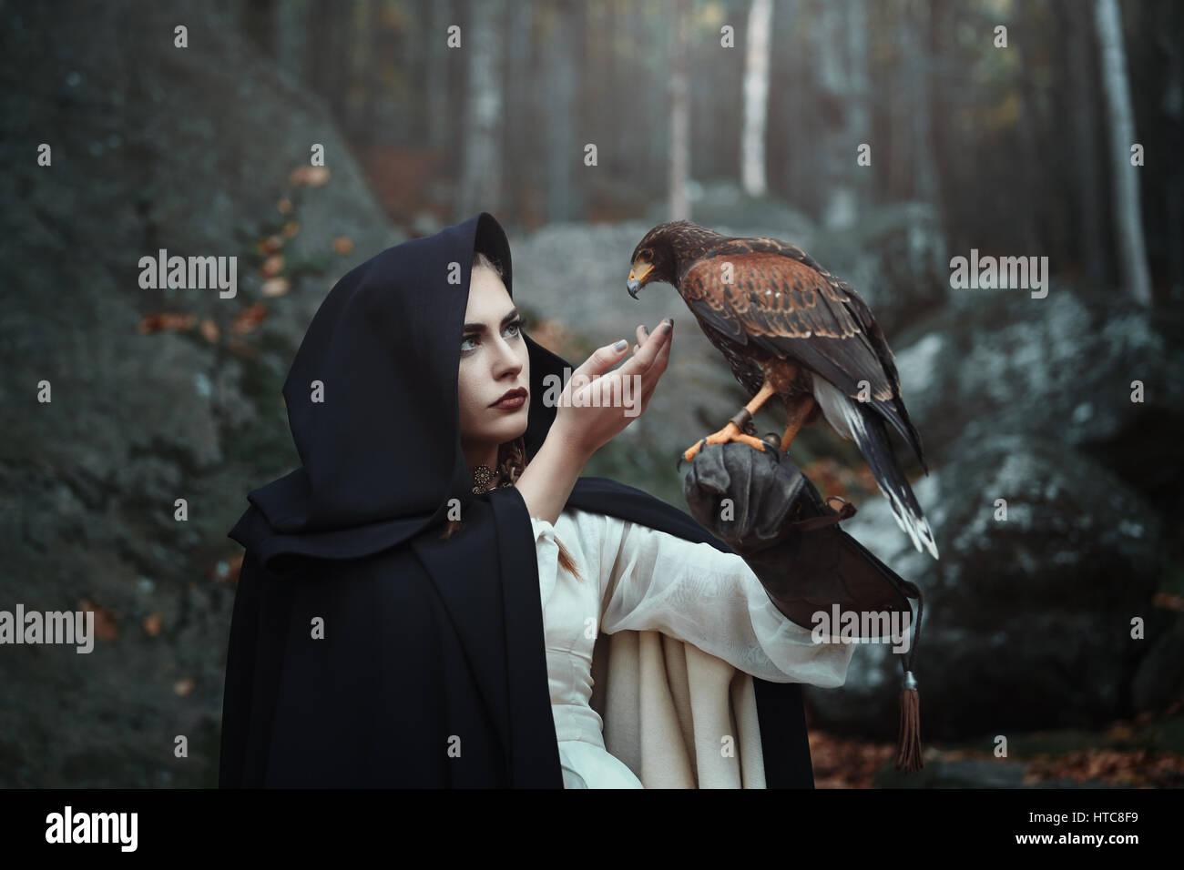 Schwarze Kapuzen Jägerin mit Hawk. Fantasie und Falknerei Stockbild