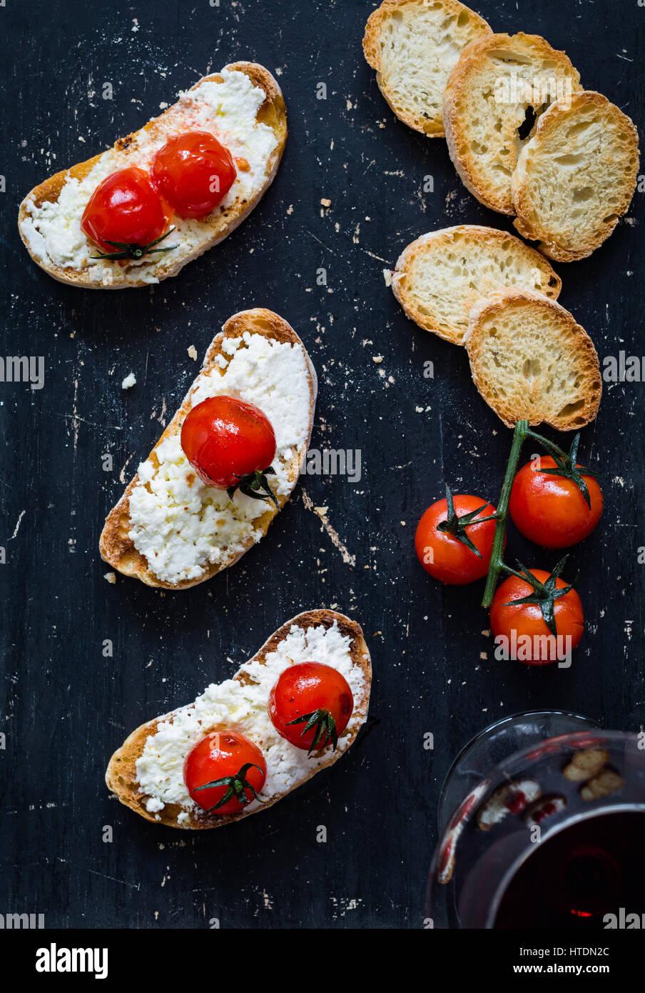 Toast mit weißen Schmelzkäse und gebratenen Kirschtomaten und Glas Rotwein bei schwarzem Hintergrund. Stockbild