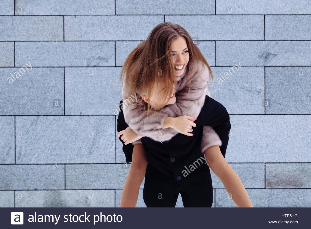 Porträt eines gutaussehenden Mann huckepack seine Freundin auf Urlaub. Stockbild