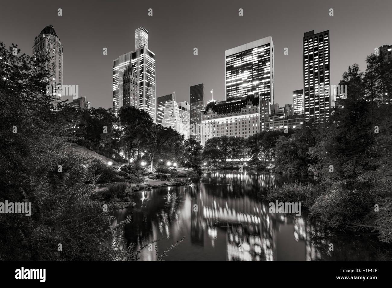 Midtown Manhattan Wolkenkratzer Abend beleuchtet. Die Gebäude des Central Park South spiegeln sich in den Teich. Stockbild