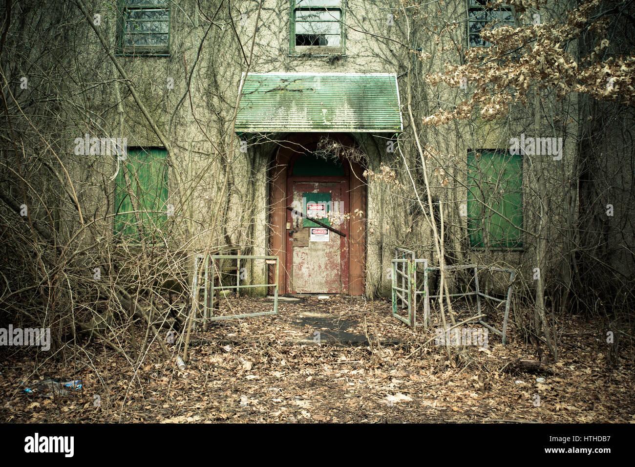 Blick auf äußere des verlassenen psychiatrischen Krankenhaus mit Asbest Warnhinweis auf Tür Stockbild