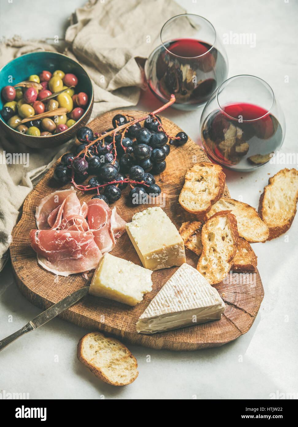 Käse, Oliven, Schinken, Baguette Scheiben, Weintrauben und Rotwein Stockbild