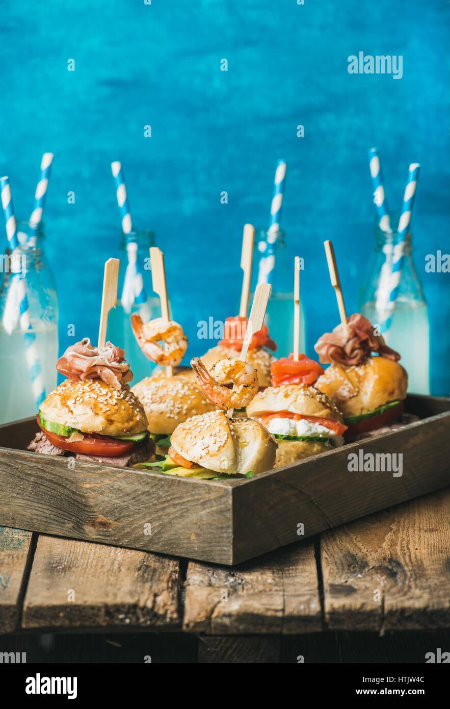Verschiedene hausgemachte Burger in Holztablett und Limonade in Flaschen Stockbild