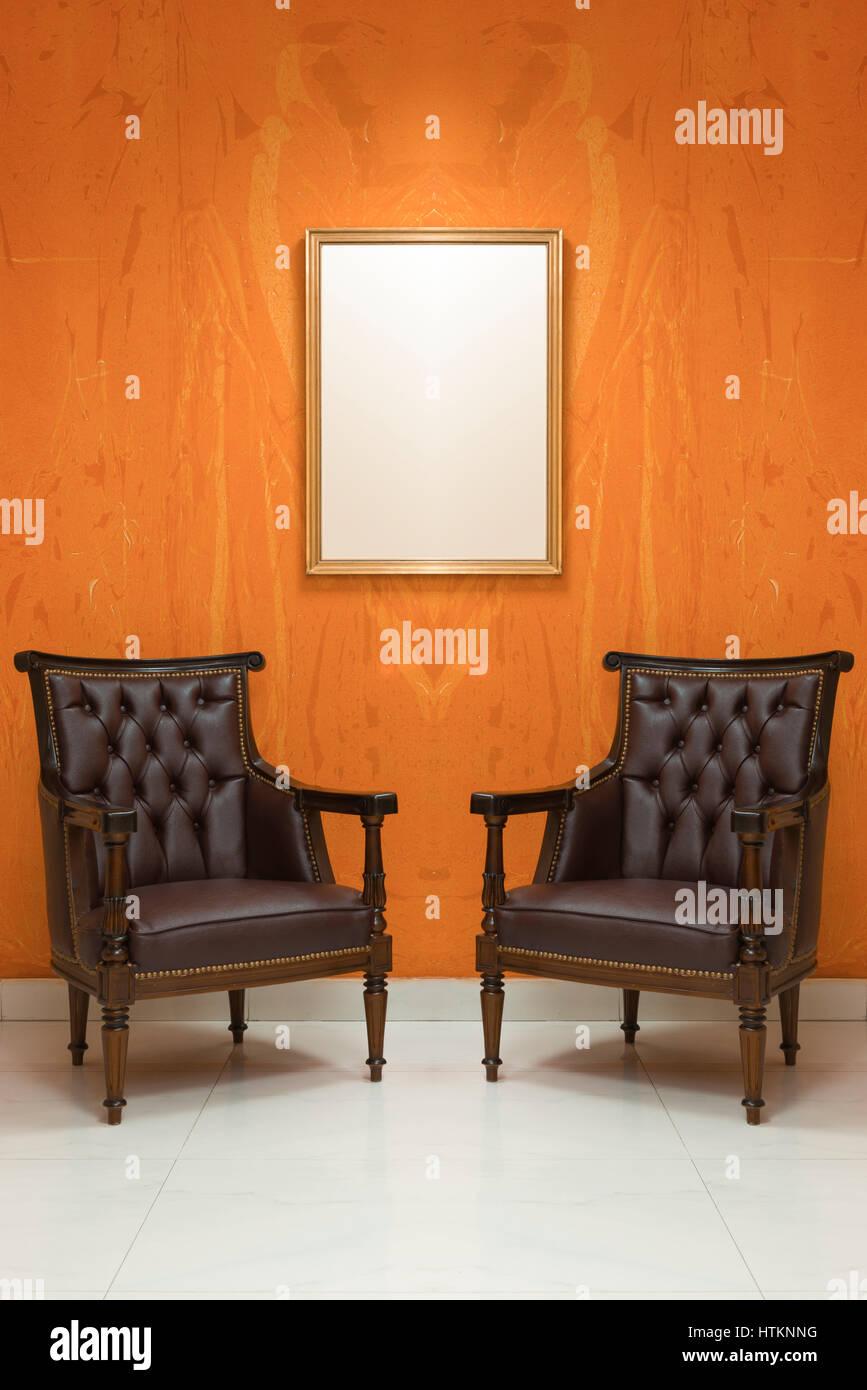 Zwei leere Stühle in einem Wohnzimmer mit Orange Wand Hintergrund ...