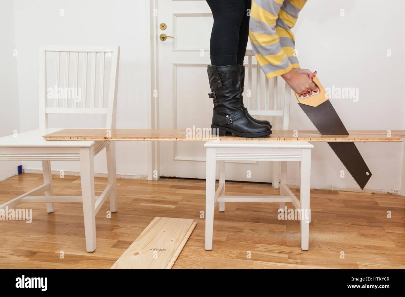 Junge Frau Tun DIY Zu Hause Griffbereit Sägen Und Holzfußböden Auf Länge  Schneiden