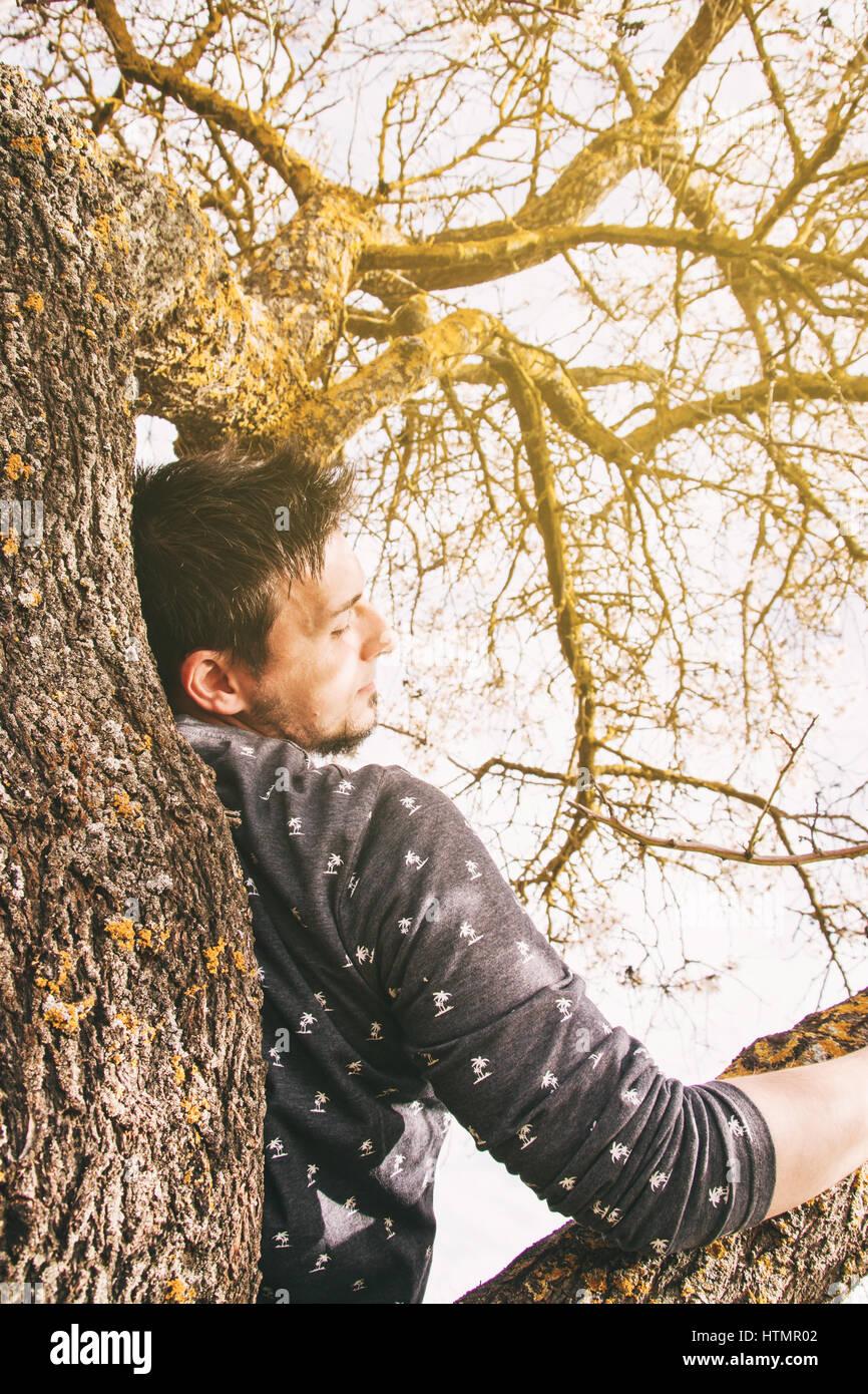 Junge Mann liegt auf der Spitze eines Baumes Stockbild