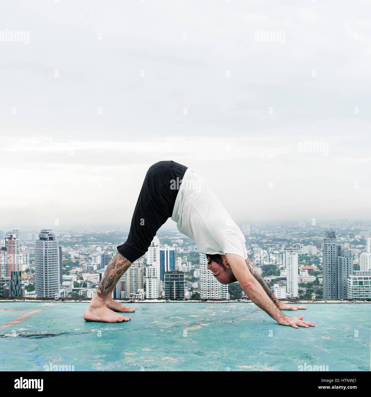 Mann Praxiskonzept Yoga auf dem Dach Stockbild