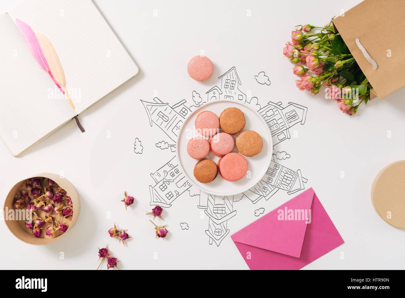 Süße Reisen. Draufsicht der Platte mit Macarones stehen auf dem Tisch in der Nähe von Pack mit Blumen Stockbild