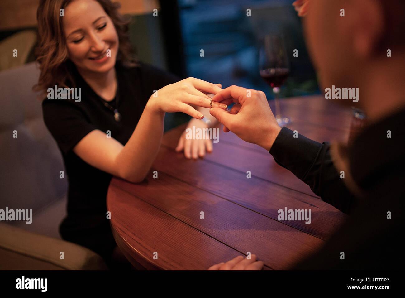 Junger Mann macht Frau Heiratsantrag und setzt ein Engagement ring an ihrem Finger. Sie sitzen am Tisch neben Gläser Stockbild