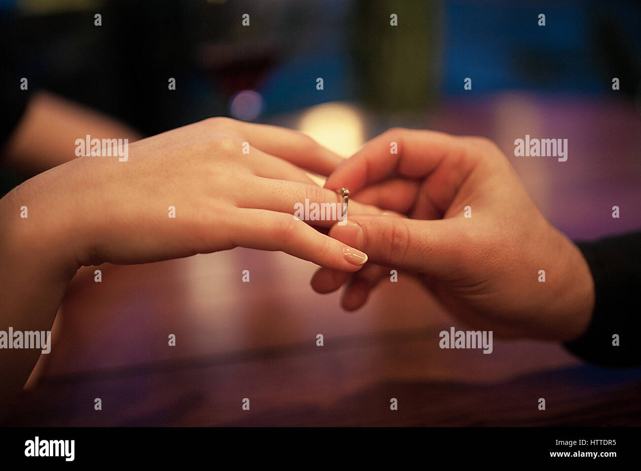 Junger Mann macht Frau Heiratsantrag und setzt ein Engagement ring an ihrem Finger. Hautnah. Sie sitzen am Tisch. Stockbild