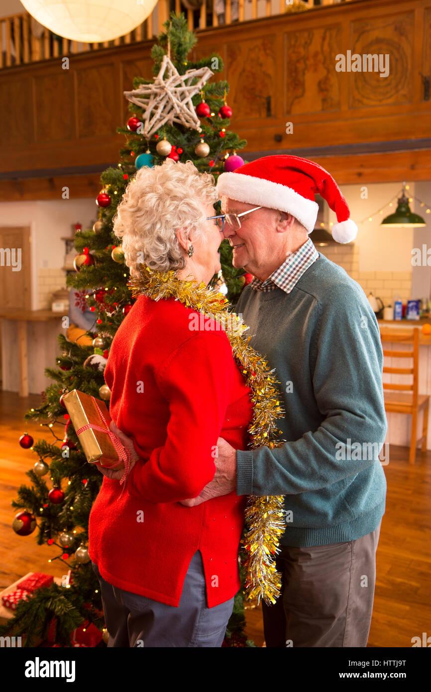 Älteres Ehepaar zu Weihnachten. Die Dame hat ein Geschenk hinter ...
