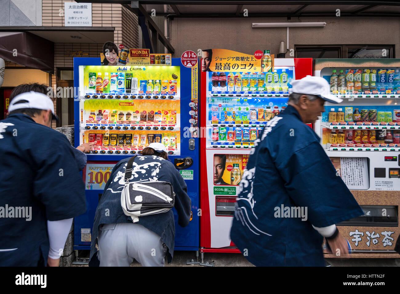 Japanische Männer mittleren Alters Kauf Getränke aus dem Automaten, Kyoto, Japan Stockbild