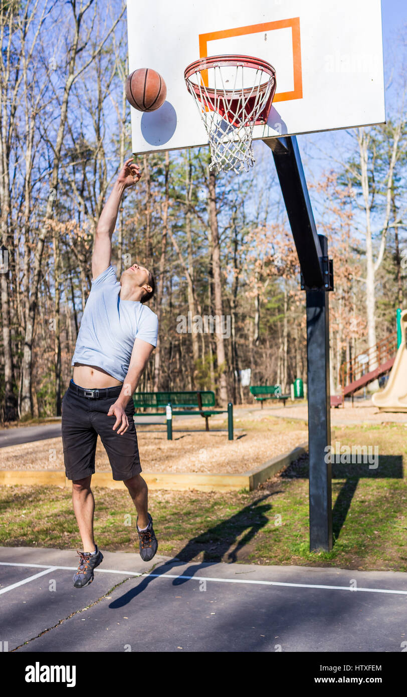 Young passen muskulösen Mann sprang werfen Basketball in Reifen Stockfoto