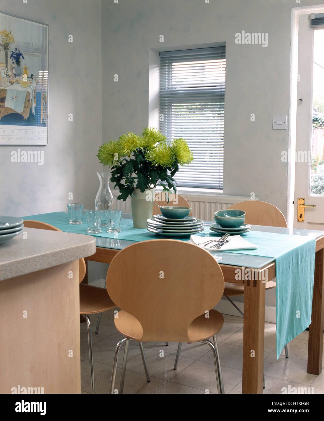 Vase mit lindgrünen Chrysanthemen auf Glastisch gekrönt mit einem ...