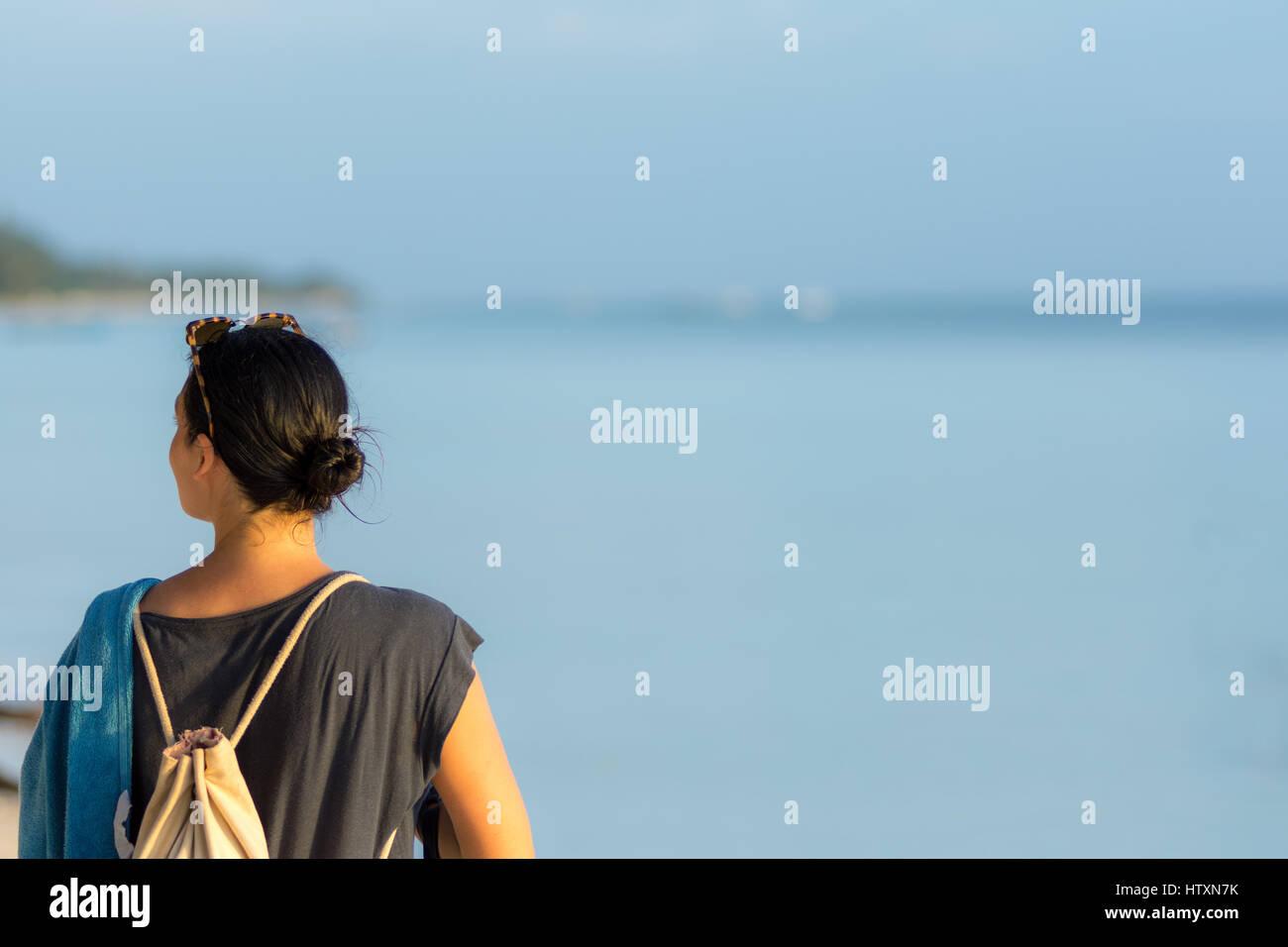 Junge schwarze behaarte Frau auf der Suche nach oben und unten am Strand mit Handtuch und Rucksack. Stockbild