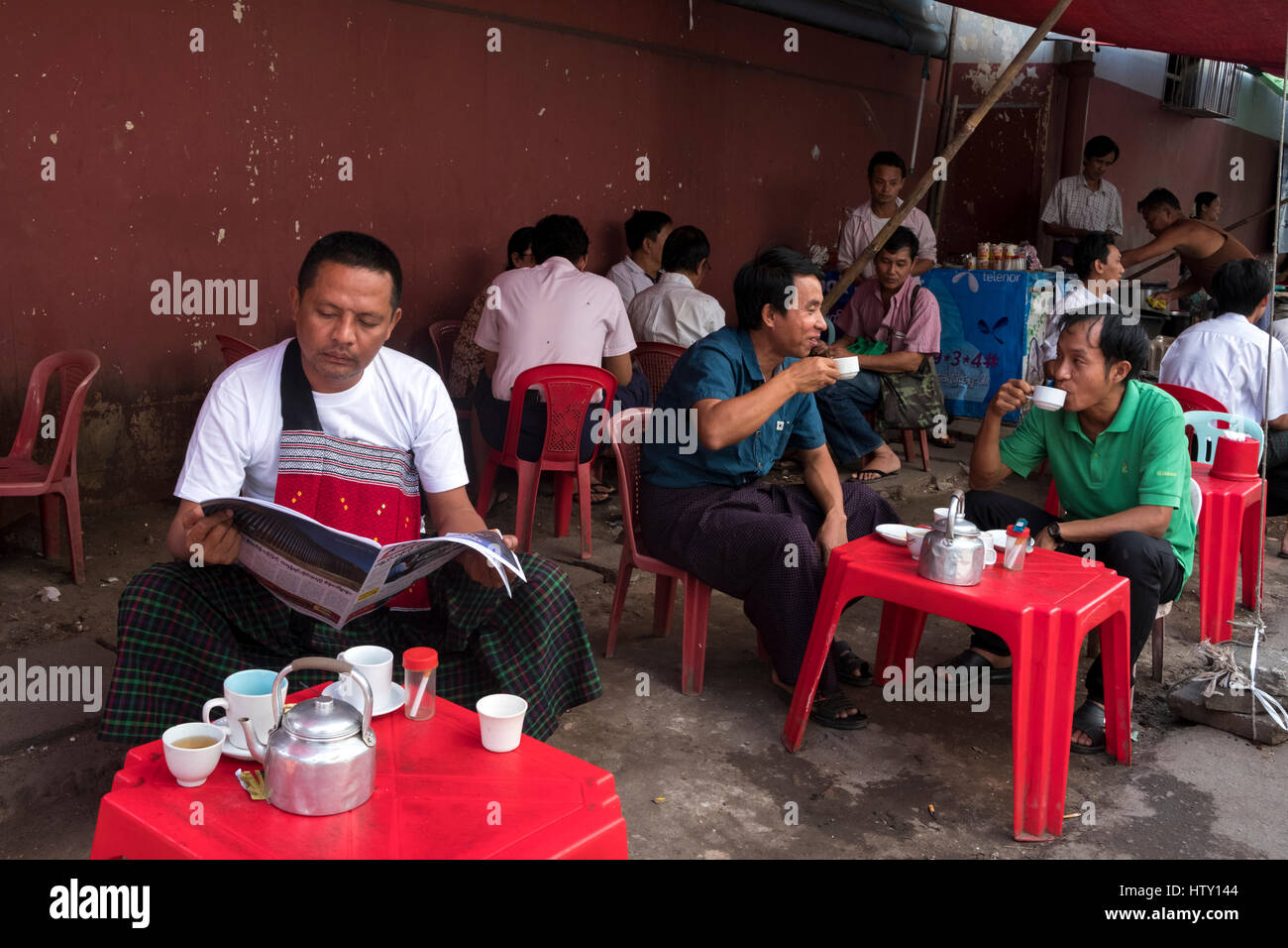 Im mittleren Alter Männer entspannen und Tee trinken in einem Stall in Pansodan Street, Yangon, Rangun Region, Stockbild