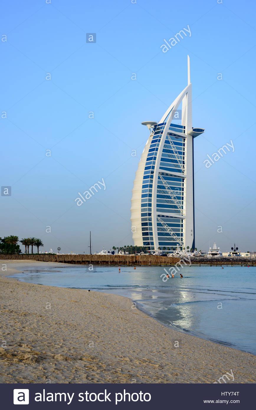 Menschen, die den offenen Strand neben dem berühmten Burj Al Arab Hotel, Dubai, Vereinigte Arabische Emirate Stockbild