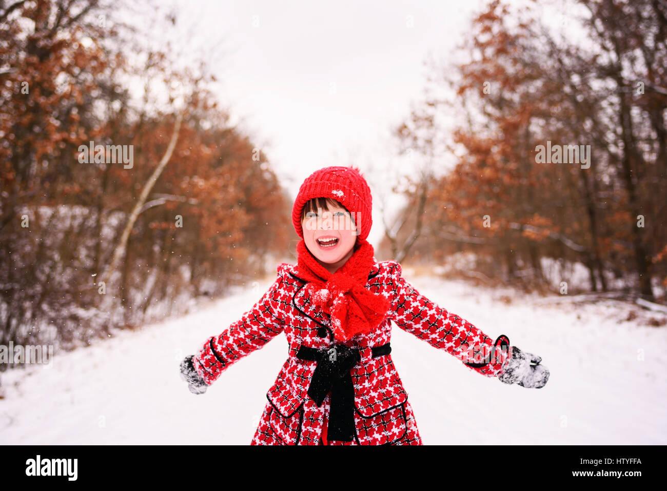 Mädchen stehen im Winterwald mit ausgestreckten Armen Stockfoto