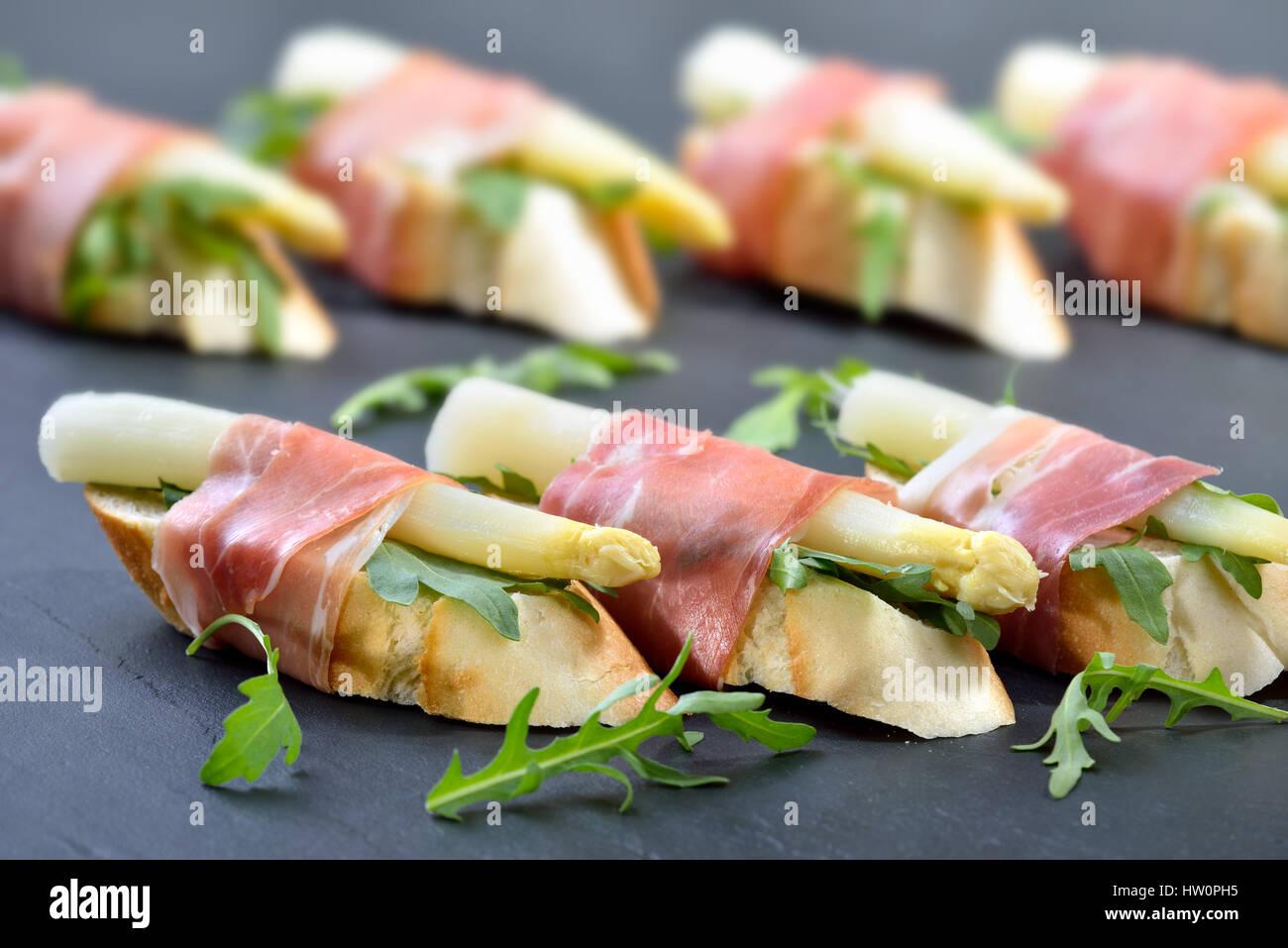 Köstliche Häppchen mit weißen Spargel auf Rucola Blätter eingewickelt mit italienischen Schinken Stockbild