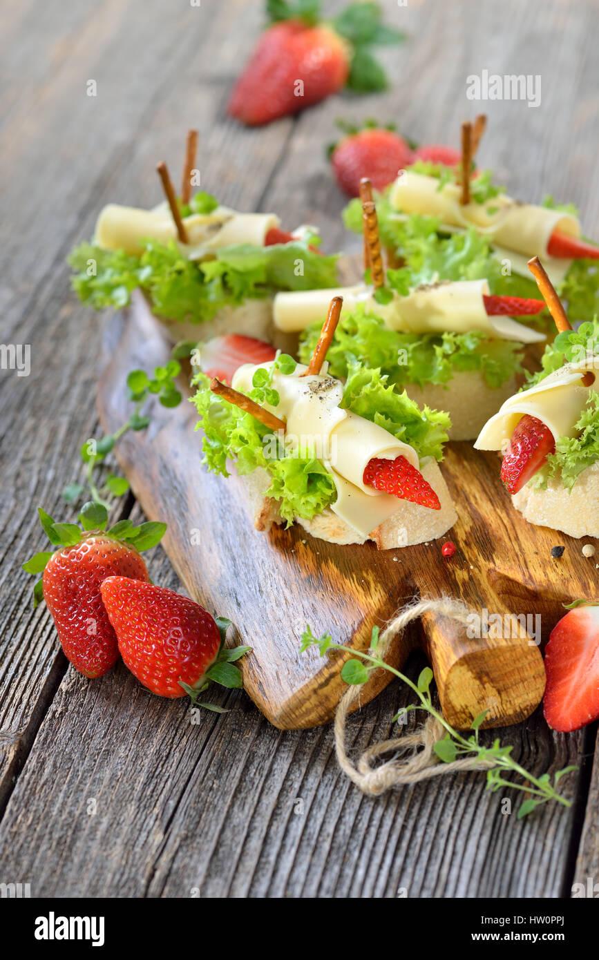 Kanapees mit leckeren Käsebrötchen und Erdbeeren auf italienische Ciabatta Brot mit Salatblättern Stockbild