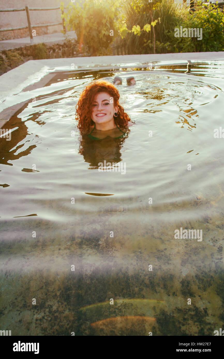 Junge rothaarige Frau genießen einen Sommertag in einem natürlichen pool Stockbild