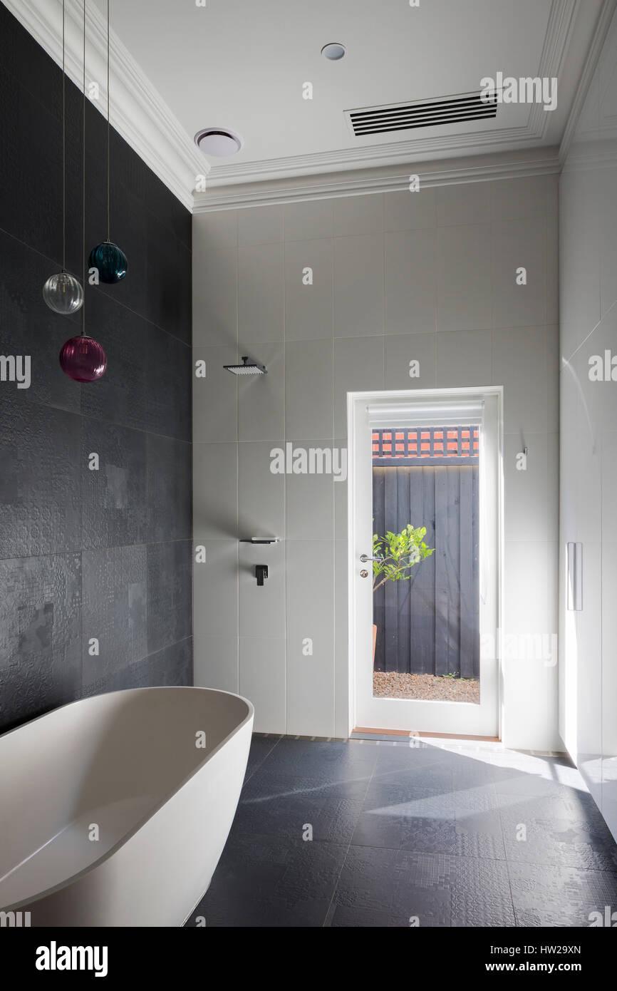 Im Erdgeschoss Badezimmer mit Badewanne, Dusche, Leuchten und Tür ...