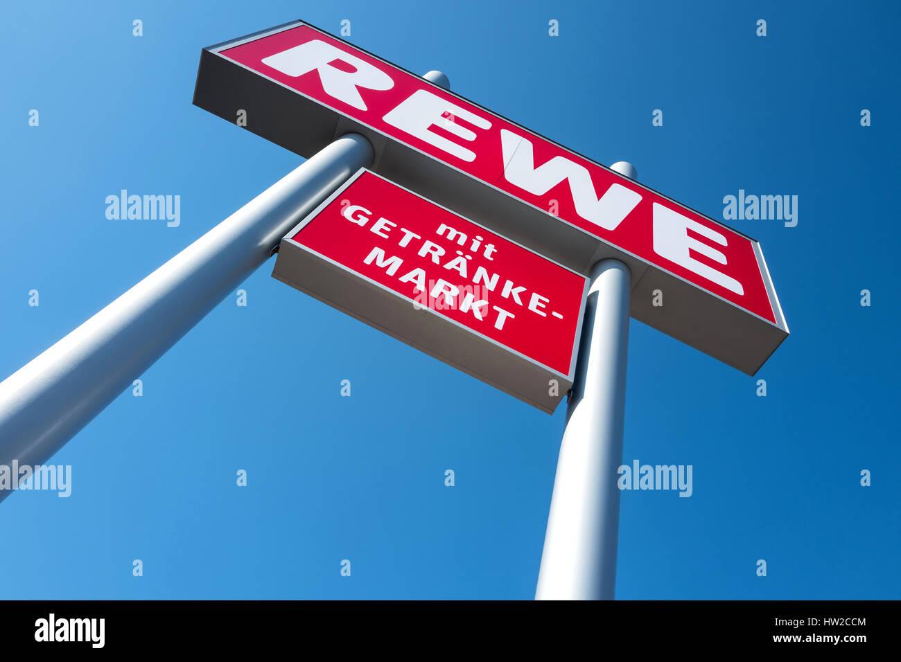 REWE-Schild (mit Getränkehandel) gegen blauen Himmel. REWE betreibt ...