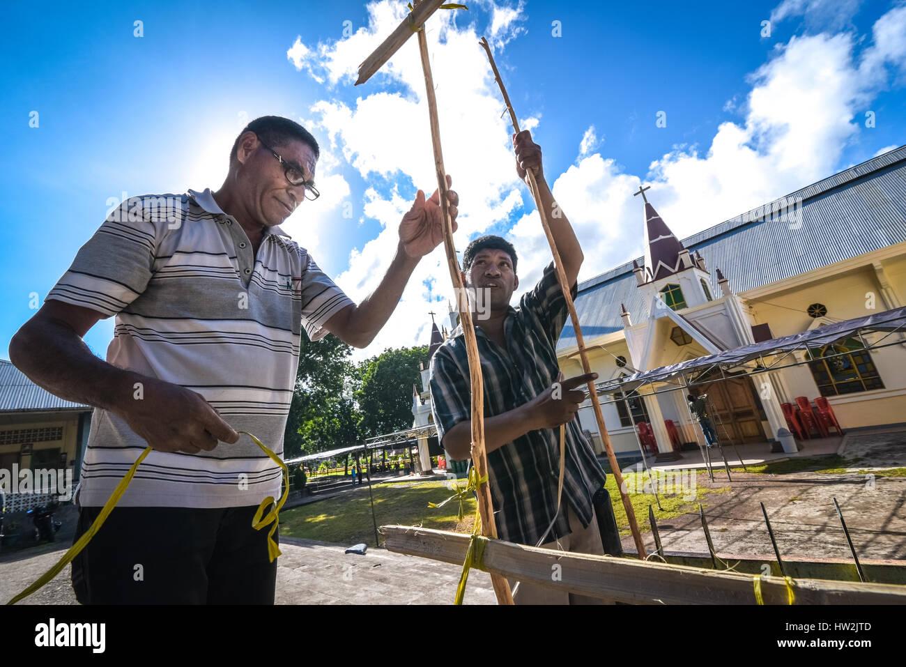 Leute bauen Bambuszäune Kerzen am Straßenrand als Vorbereitung für die Karwoche-Zeremonie in Larantuka, Stockbild