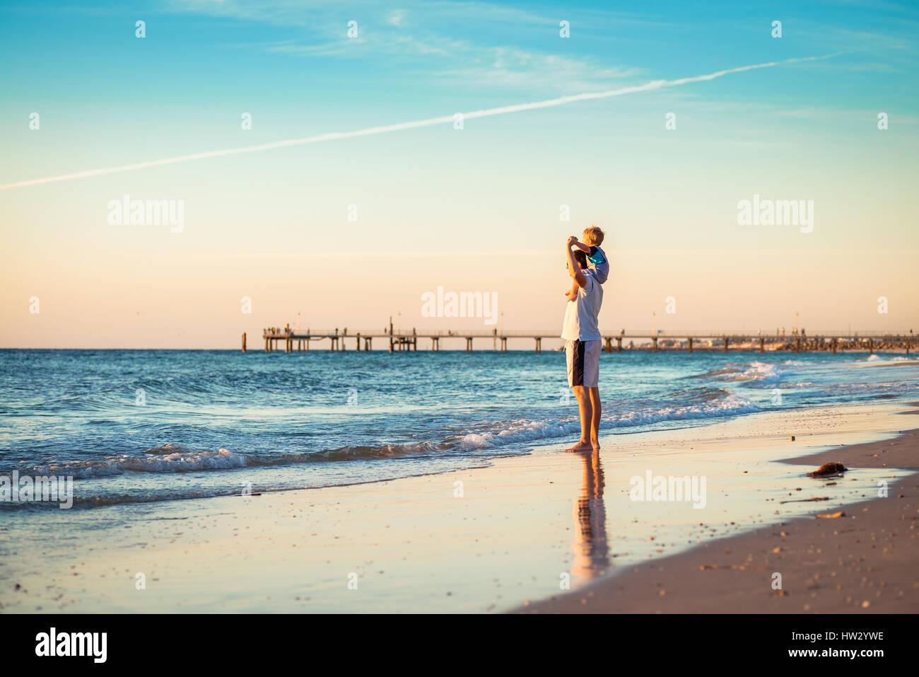 Vater und Sohn Huckepack Reiten am Strand Stockbild