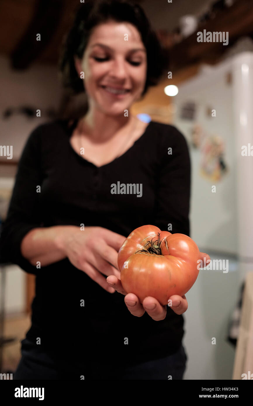 Junge rumänische Frau hält eine große Heirloom-Tomate wuchs sie in ihrem Garten in Saschiz, Rumänien. Stockbild
