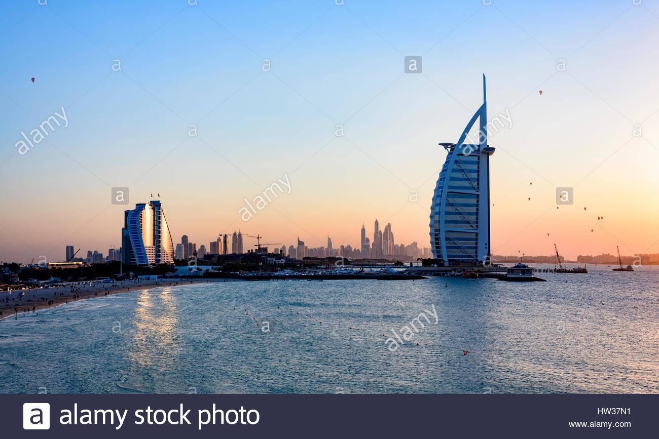 Jumeirah Beach Hotel und das berühmte Burj Al Arab Hotel mit Heißluftballons vorbei hinter es bei Sonnenuntergang, Stockbild