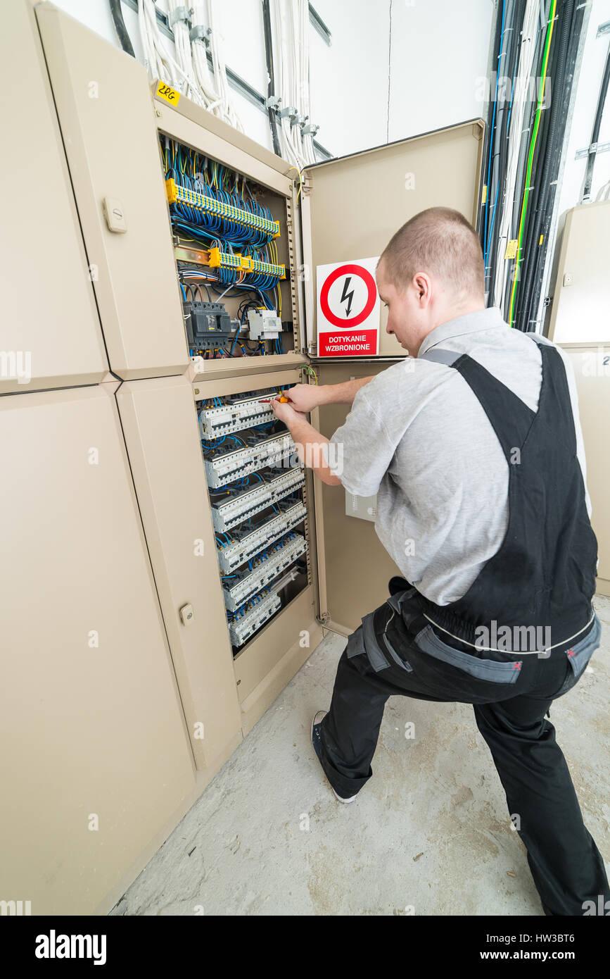 Elektriker verschärft Sicherungen in der Schalttafel Stockbild